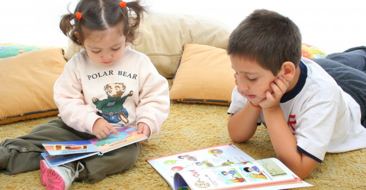 Brother and sister reading books over a carpet. They look interested and concentrated. Visit my gallery for more images of children