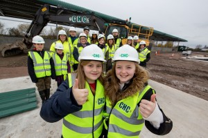 Brownies Grace and Ava (foreground) with families in background, accompanied by staff from MRWA and Cheetham Hill Construction.
